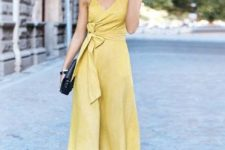 04 a stylish yellow linen midi wrap dress with a bow on the side, comfy low heels and a black clutch
