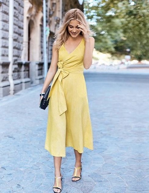 a stylish yellow linen midi wrap dress with a bow on the side, comfy low heels and a black clutch