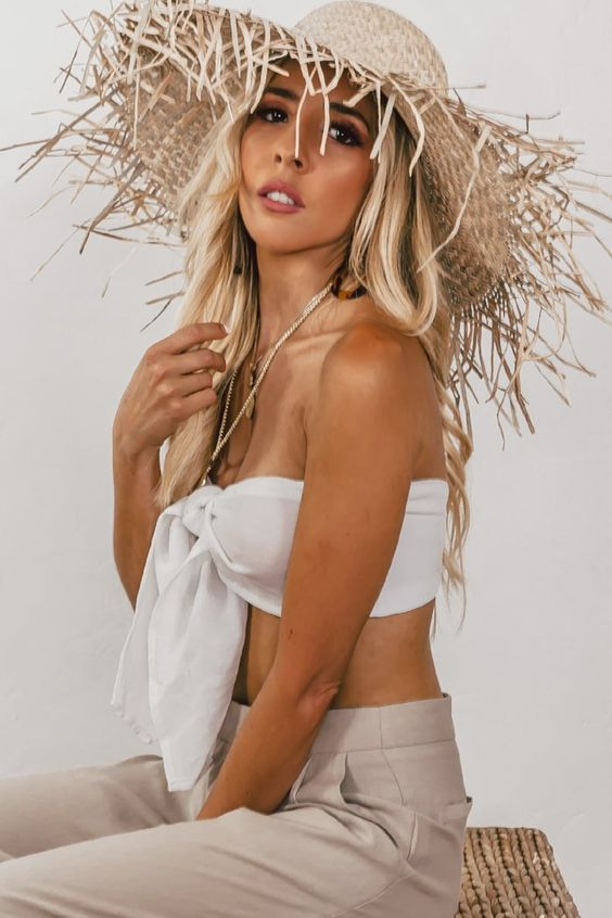 a swimsuit top, neutral pants and a fringe brim hat to go on a vacation