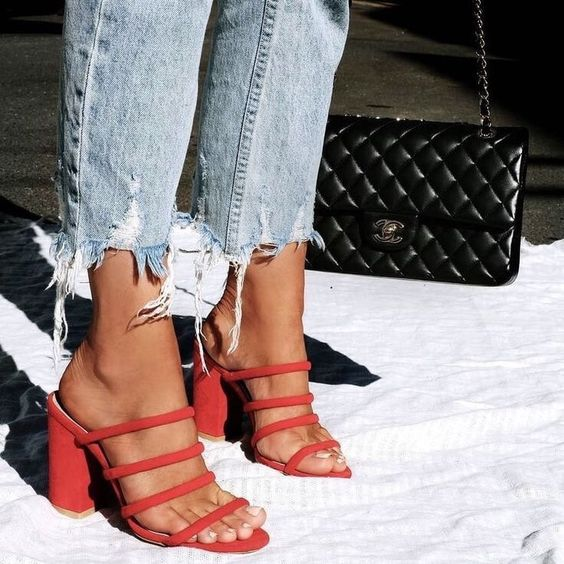 light blue jeans with a ripped hem paired with red strappy mules with square toes