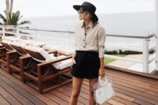 05 a beige button down, a black mini shorts, brown slippers, a black hat and a clear and white bag