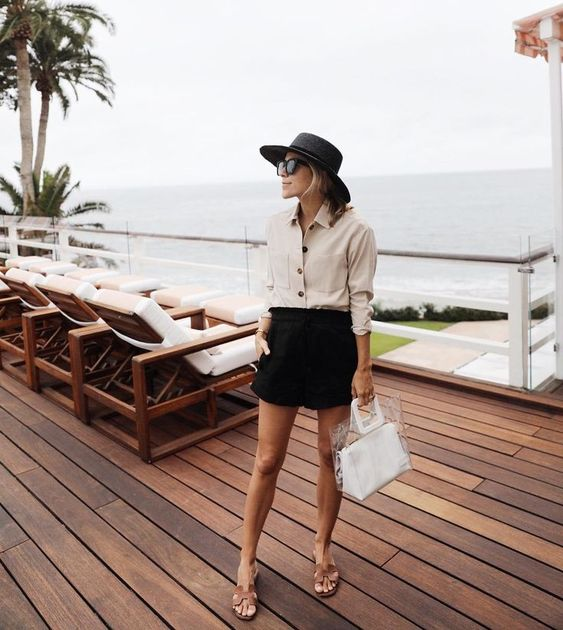 a beige button down, a black mini shorts, brown slippers, a black hat and a clear and white bag