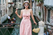 05 a pink linen midi dress with a knot bodice, spaghetti straps, buttons, strappy sandals and a straw bag