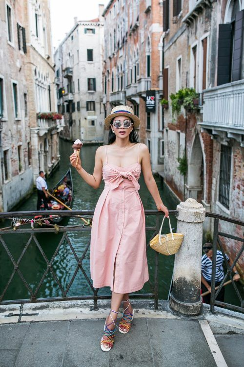 a pink linen midi dress with a knot bodice, spaghetti straps, buttons, strappy sandals and a straw bag