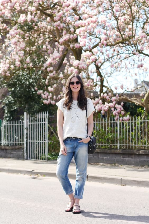 a white crochet tee, blue jeans, metallic dad sandals and a black bag for a comfy look