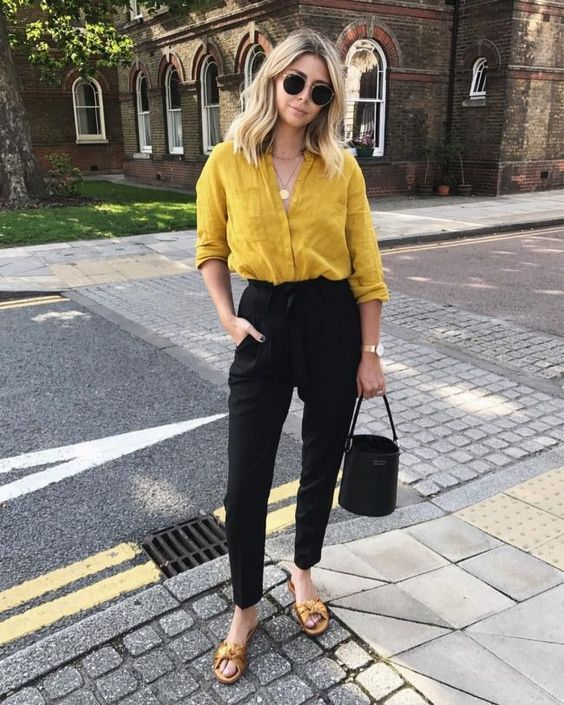 a chic work look with a mustard button down, black pants, mustard bow slippers and a black bucket bag