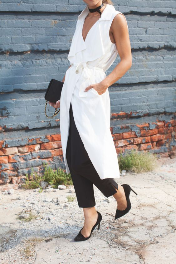 a cool summer work outfit with a long white sleeveless jacket, black pants, black shoes and a black clutch for a bright summer work look