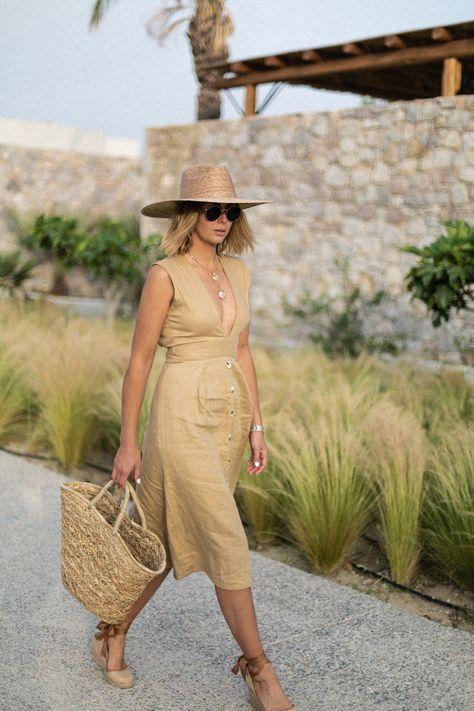 a nude linen midi dress with a plunging neckline, espadrilles, a straw hat and a straw bag