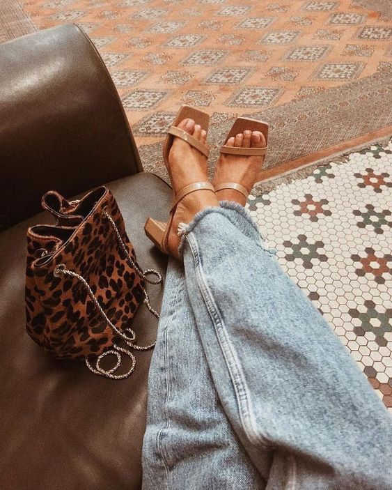 light blue distressed jeans paired with tan strappy mules with square toes are a cool combo