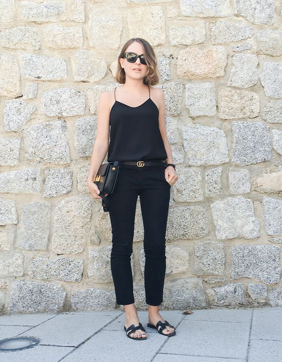 a total black look with a spaghetti strap top, black cropped pants, black slippers and a black bag