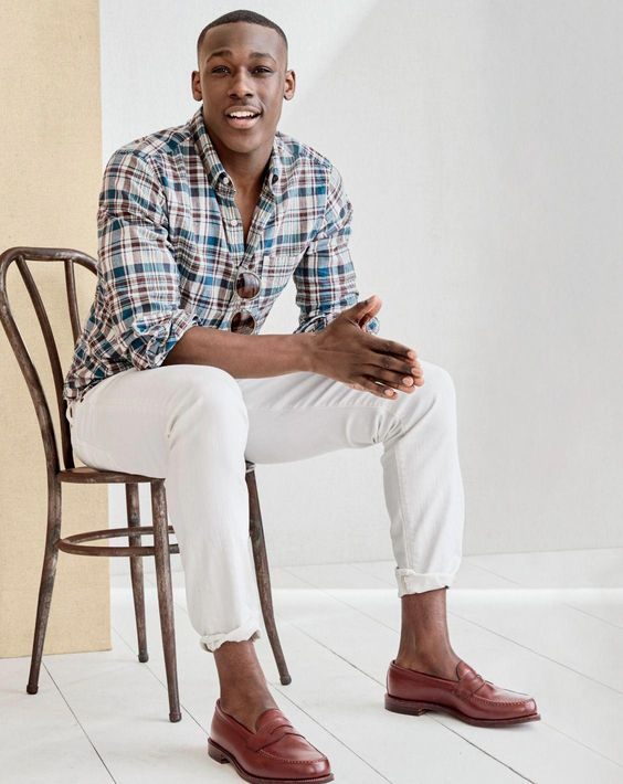 a casual summer look with a bright checked shirt, white pants, brown loafers and sunglasses for a hot day