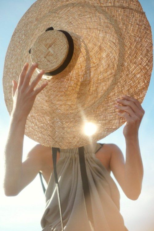 a grey dress paired with an oversized straw hat with a black ribbon to make a statement with a stylish accessory