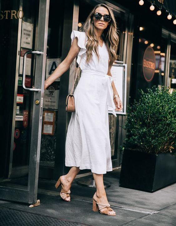 a white linen midi dress with ruffle sleeves, a V-neckline, a sash, knot mules and a brown bag