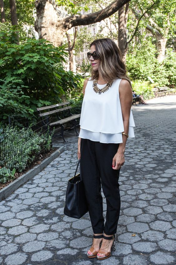 a white sleeveless layered top, black pants, black and brown shoes and a black tote