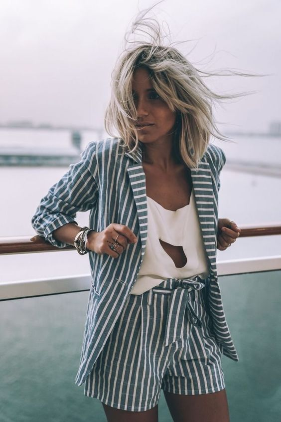a beach inspired short suit with blue and white stripes, a white cutout top and statement bracelets