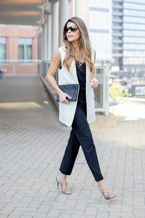 a black strap jumpsuit, a white waistcoat, printed shoes and a black clutch are a stylish option