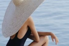 09 a black swimsuit with a cutout back is paired with a white oversized straw hat to make up a monochromatic and wow look