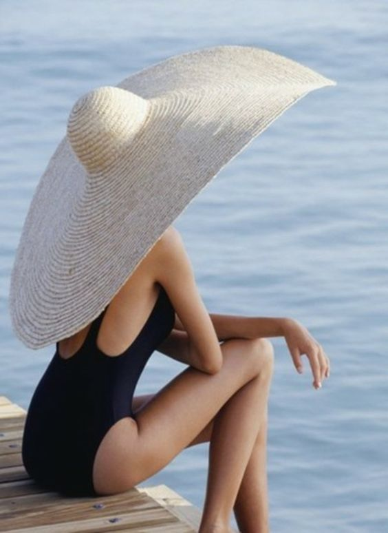 a black swimsuit with a cutout back is paired with a white oversized straw hat to make up a monochromatic and wow look