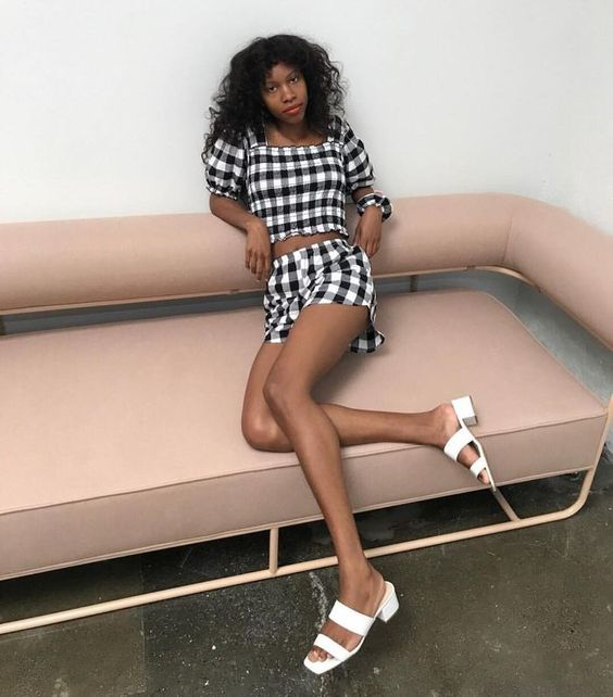 a bold black and white plaid suit with a crop top with puff sleeves and shorts plus white square toe shoes