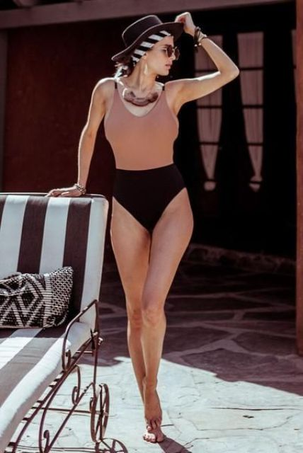 a chic dusty pink and black one piece swimsuit with straps and a scoop neckline