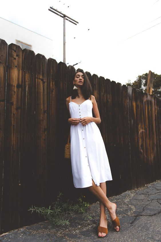 a white linen midi dress with straps and buttons, brown slippers and a brown bag