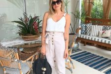 09 a white strap top, blush high waisted pants with buttons, black slippers and a black bag
