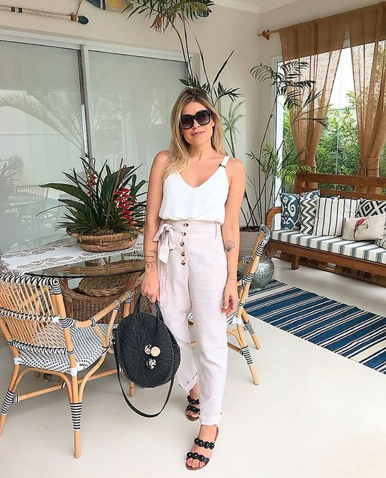 a white strap top, blush high waisted pants with buttons, black slippers and a black bag