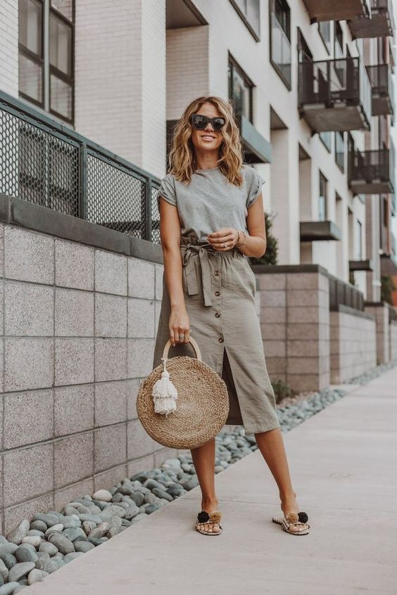 a grey tee, a tan midi high waisted skirt with buttons, pompom slippers and a straw bag