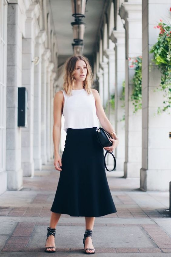 a black midi, a white sleeveless top, black sandlas and a black clutch are a perfect combo