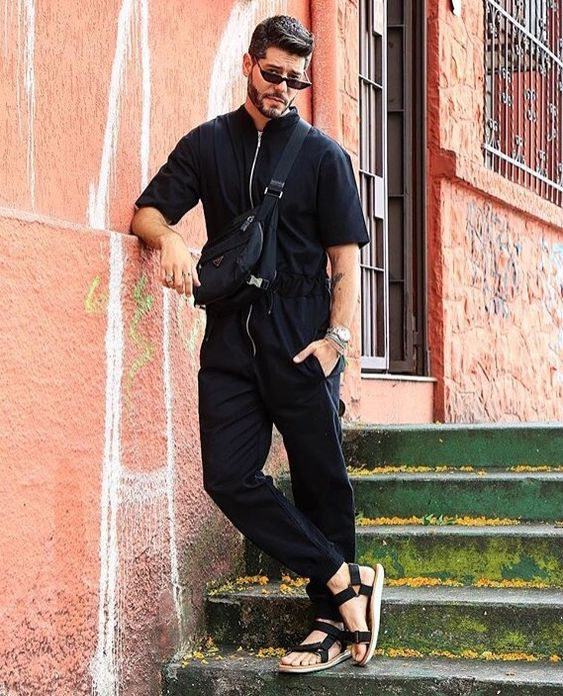 a total black look with pants, a shirt with a zipper, sandals and a crossbody for a more masculine look