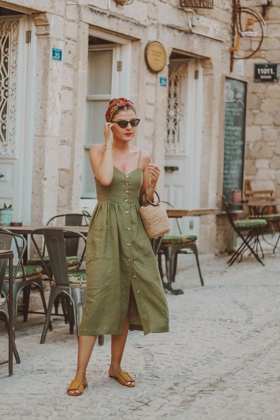 an olive green spaghetti midi dress with a row of buttons, brown slippers, a straw bucket bag