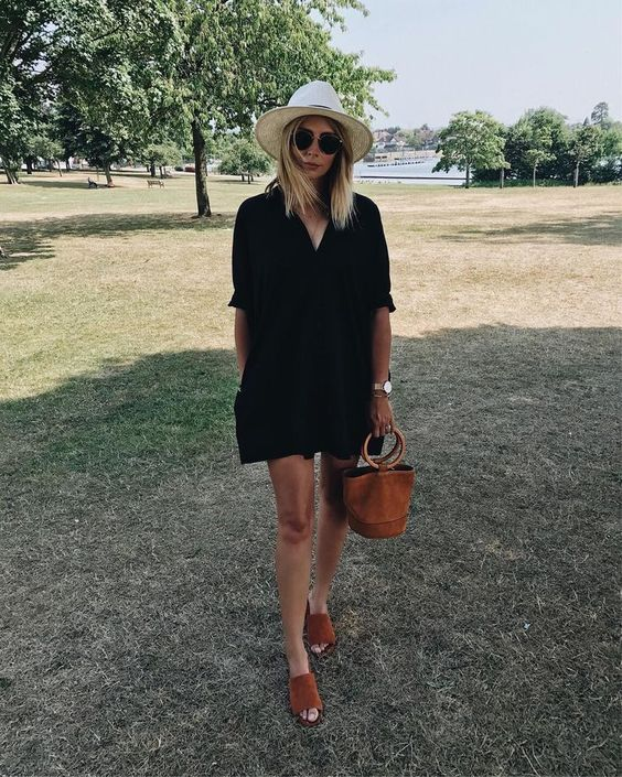 a black shirtdress, brown slipper mules and a brown leather bucket bag plus a straw hat