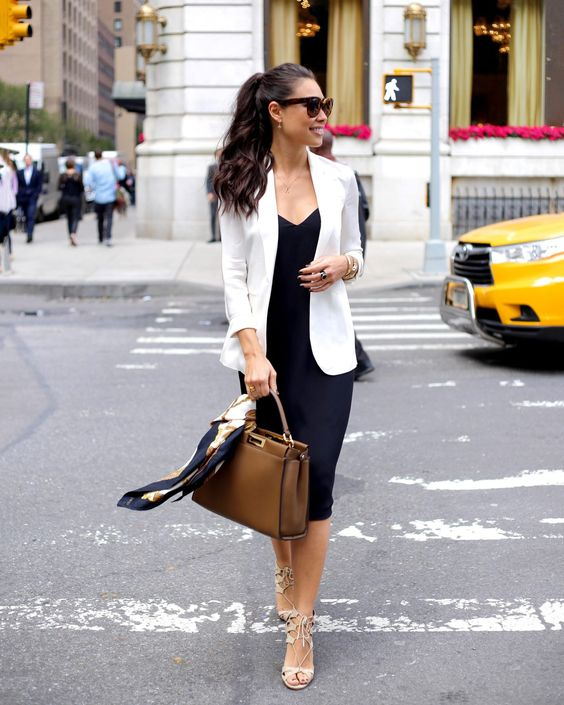 a black slip dress, a white blazer, nude heels and a brown bag for a stylish summer work look