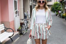 12 a fun and colorful stripe short suit, a white tee, pink sneakers and a white round bag for summer