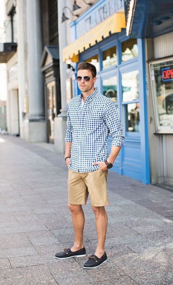 a preppy summer look with a white tee, a blue checked shirt, tan shorts and navy loafers