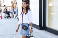 12 a white button down, a blue denim mini skirt with an asymmetrical edge, black slippers and a black crossbody