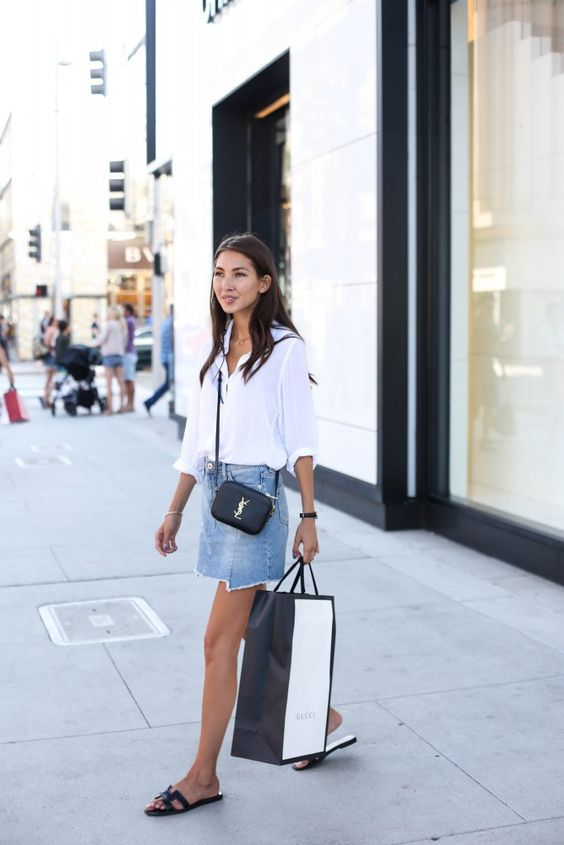 a white button down, a blue denim mini skirt with an asymmetrical edge, black slippers and a black crossbody