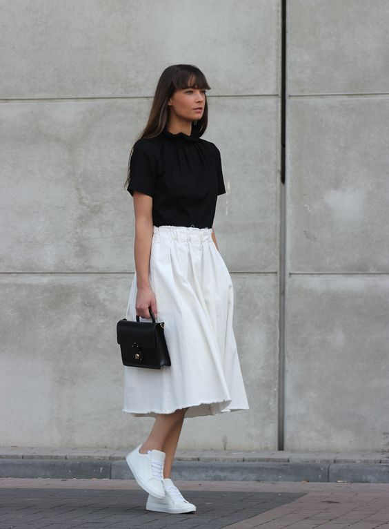 a black tee, a white full midi skirt, white sneakers and a small black bag make up an outfit wiht a casual feel