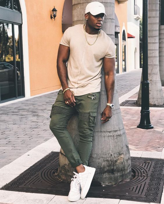 a neutral tee, olive green cargo pants, white sneakers and a neutral cap for a sporty look