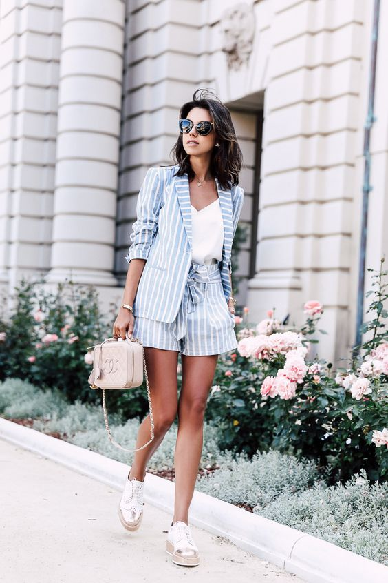 a powder blue striped suit, a white top, neutral sneakers and a blush bag for a holiday or office