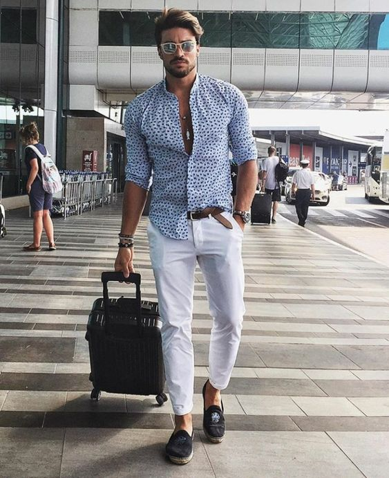 a relaxed holiday look with a blue printed shirt, white pants, dark loafers with embroidery