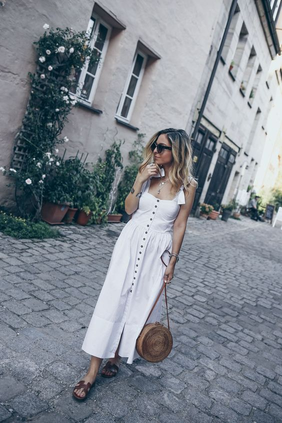 a white midi dress with ties on the shoulders and a row of blakc buttons, brown slippers and a wicker round bag