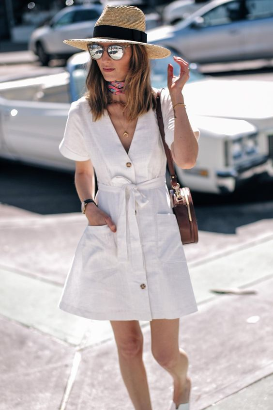 a comfy white linen short sleeve over the knee dress with buttons, a straw hat and a brown bag