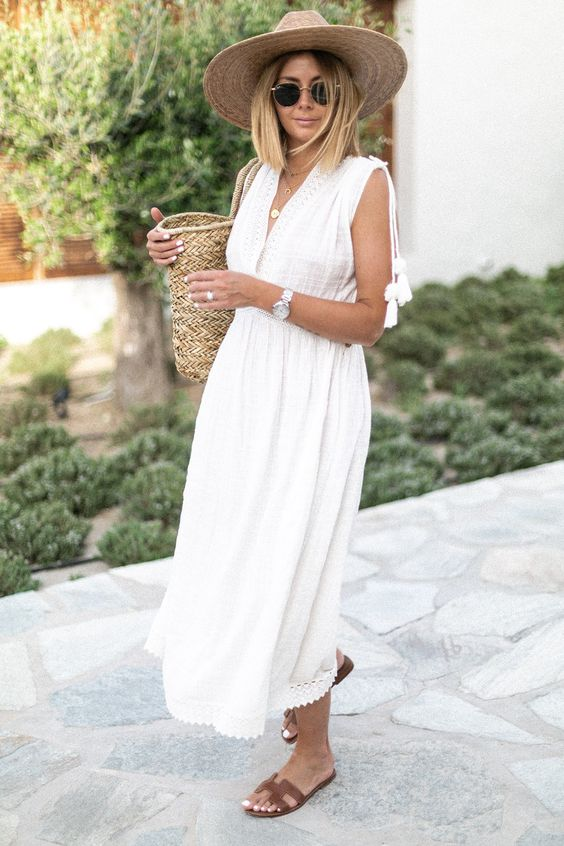 a white sleeveless linen midi dress with a plunging neckline, tassels, brown slippers and a straw bag