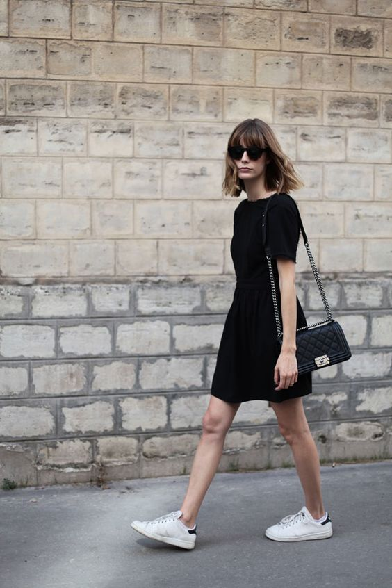a casual summer work outfit with a little black dress with short sleeves, a black bag and white sneakers for a casual work look