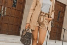 15 a tan suit with high waisted shorts, a grey tee, white V-cut slingbacks and a printed bag