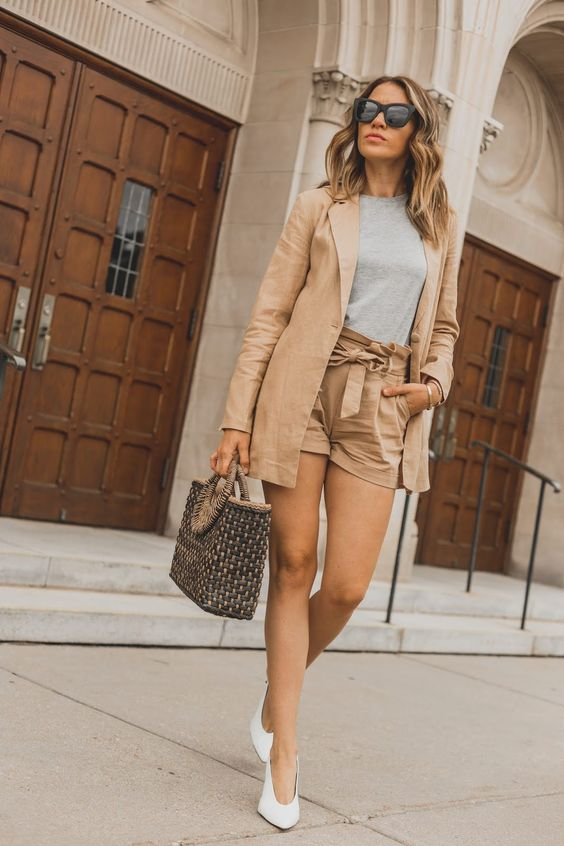 a tan suit with high waisted shorts, a grey tee, white V-cut slingbacks and a printed bag