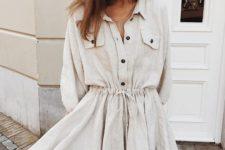16 a neutral linen shirtdress with a waist, black buttons, pockets and a straw bag