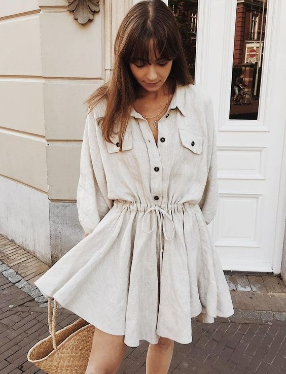 a neutral linen shirtdress with a waist, black buttons, pockets and a straw bag