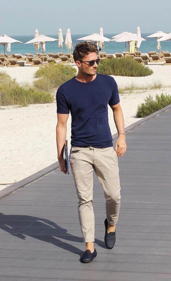 a simple summer outfit with a navy tee, tan pants and black loafers